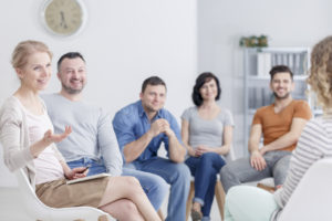 Group listening to the woman during psychotherapy session